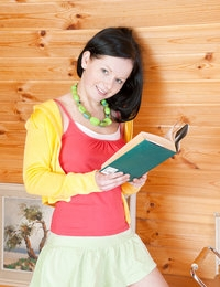 Charming dark haired teen with beads on her neck taking off clothes and demonstrating body.