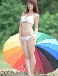 Fascinating redhead nymph with impressive tits posing with a big gaudy umbrella outdoors.