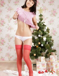 Wonderful honey with splendid tits in red stockings showing shaved cunt near New Year tree.