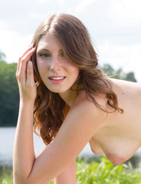 Sexy brunette spreads her legs in the sunshine by the pond, feeling true lustfulness and passion while she does poses.