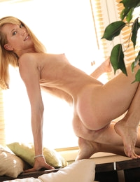 Amber exudes sex and candy while nude and beautiful by the plant