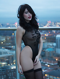 Ava Delush in black lingerie outdoors on a cloudy day.