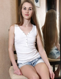 Skinny blonde teen Larisa taking off her clothes